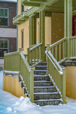Entrance of a home in Daybreak Utah viewed on a snowy winter day in December. The falling snow creates a frosty blanket of snow on the ground and stairs.
