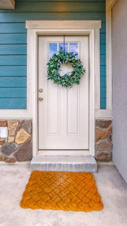 Fachada vertical clara de una casa con una simple corona de hojas colgando de la puerta de entrada blanca. Un felpudo tejido marrón está en el umbral de la puerta con una luz de techo en el techo.