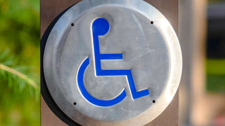 Clear Panorama Close up of a Disabled Sign engraved on a circular metal viewed on a sunny day. The sign indicates an area that is adapted for wheelchair users.