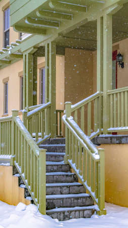 Clear Vertical Stairs going to the front porch of a charming home in Daybreak Utah. The entryway is covered with fresh snow on this cold winter day in December.