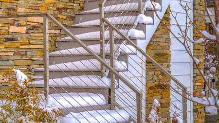 Panorama Snowy outdoor stairs of home in Daybreak Utah. Outdoor stairs of a home in Daybreak, Utah covered with snow in winter. A snow topped picket fence can be seen in the foreground. Imagens