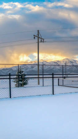 Vertical Tennis courts on a landscape blanketed with snow during winter season. A stunning snow capped mountain against cloudy sky at sunset can be seen in the distance.