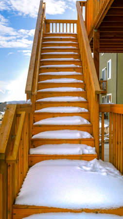 Clear Vertical Outdoor wooden staircase of a home covered with snow during winter season. A scenic view of homes, snow capped mountain, and blue sky with puffy clouds can be seen in the background.