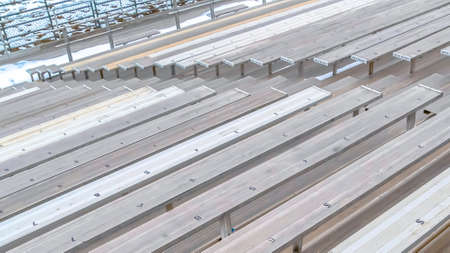 Panorama Bleachers with numbers on the surface viewed on a sunny winter day. A snow covered field can be seen at the bottom of the tiered seating. Stock Photo