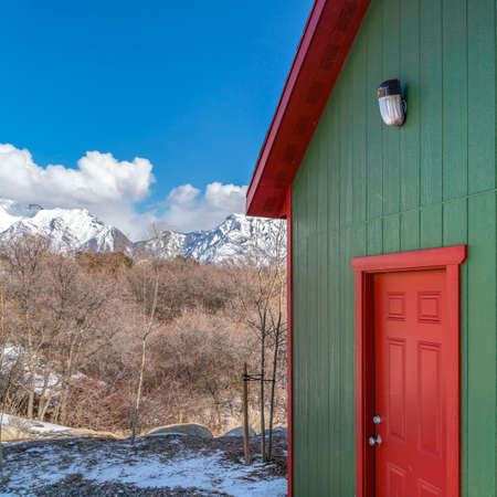 Square Exterior of a storage shed with a lamp on the green wall above the red door. In the background are trees and snow capped mountain under a cloudy blue sky on a sunny winter day. Фото со стока