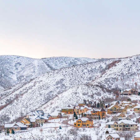 Square Scenic panorama of houses built on a mountain with cloudy sky bakground. The homes and mountain are blanketed with fresh powdery snow in winter.