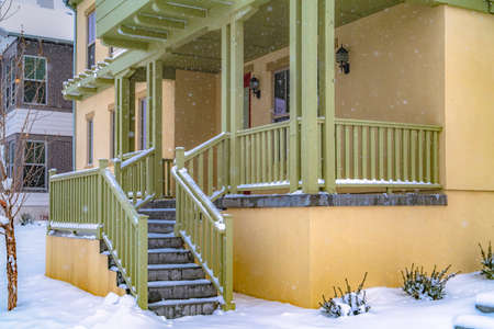 Stairs going to the front porch of a charming home in Daybreak Utah. The entryway is covered with fresh snow on this cold winter day in December. Imagens
