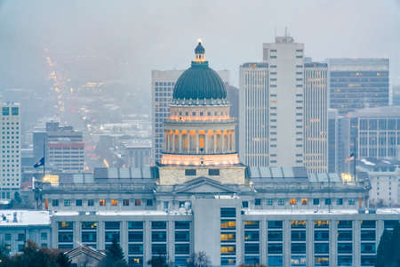 The magnificent Utah State Capital Building in Salt lake City on a hazy day. Skyscrapers and the populous downtown can be seen behing the iconic building.