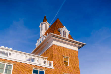 Exterior view of a building against vibrant blue sky on a bright sunny day. A contrail can also be seen behind the sunlit roof and steeple of the building.