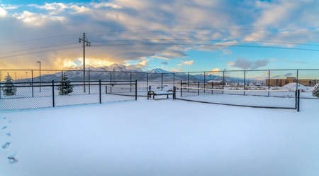 Tennis courts on a landscape blanketed with snow during winter season. A stunning snow capped mountain against cloudy sky at sunset can be seen in the distance.