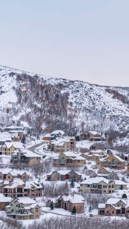 Vertical Scenic panorama of houses built on a mountain with cloudy sky bakground. The homes and mountain are blanketed with fresh powdery snow in winter.