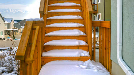 Clear Panorama Outdoor wooden staircase of a home covered with snow during winter season. A scenic view of homes, snow capped mountain, and blue sky with puffy clouds can be seen in the background. Stok Fotoğraf