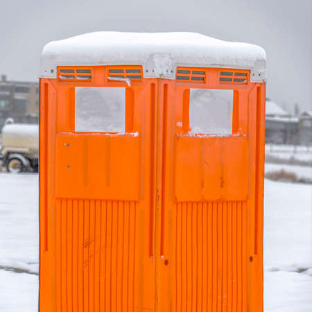Square Close up view of a bright orange portable restroom in Daybreak Utah. A landscape covered with snow in wwinter can be seen behind the movable toilet.