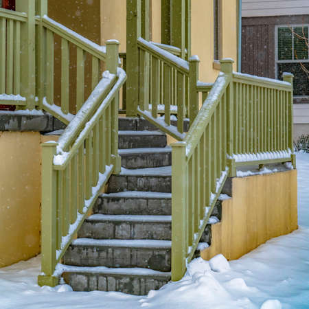 Square Entrance of a home in Daybreak Utah viewed on a snowy winter day in December. The falling snow creates a frosty blanket of snow on the ground and stairs. Stok Fotoğraf