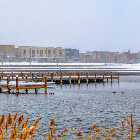 Square Buildings against sky on a snow covered landscape beyond the lake in winter. Snowy wooden decks can also be seen above the water with grasses in the foreground.