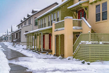 Pathway in front of cozy homes in Daybreak Utah viewed in winter. The snow falling from the cloudy sky creates a blanket of frost on the landscape.