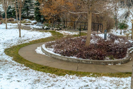 A beautifully landscaped park in Salt Lake City blanketed with snow in winter. The relaxing park features winding paths, trimmed lawn, lush trees, and frosty slope.