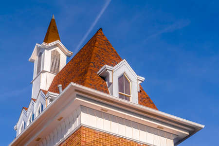 Roof and steeple of a building with vibrant blue sky in the background. A contrail can also be seen behind the brick building on this sunny day.