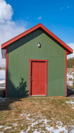 Clear Vertical Small wooden storage shed with a lamp on the green wall above the red door. The terrain surrounding the shed is covered with snow on a sunny winter day.