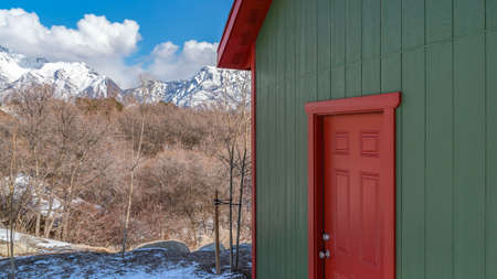 Clear Panorama Exterior of a storage shed with a lamp on the green wall above the red door. In the background are trees and snow capped mountain under a cloudy blue sky on a sunny winter day.