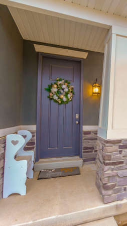 Clear Vertical Gray front door on the facade of a home decorated with bauble and flower wreath. Benches and doormats are placed on the cozy porch with large pillars.