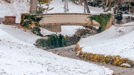 Clear Panorama Stream and bridge on a lovely snow covered park in Salt Lake City in winter. The winding stone lined stream passes under a stone bridge with trees in the background.