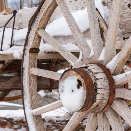 Square Close up of the rusty wheels of a weathered wooden wagon viewed in winter.The wagon and surrounding landscape is covered with fresh powdery snow.