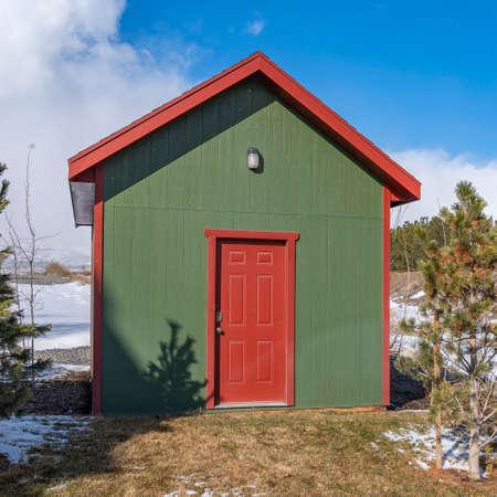 Cuadrado Pequeño cobertizo de madera con una lámpara en la pared verde sobre la puerta roja. El terreno que rodea el cobertizo está cubierto de nieve en un soleado día de invierno. Foto de archivo