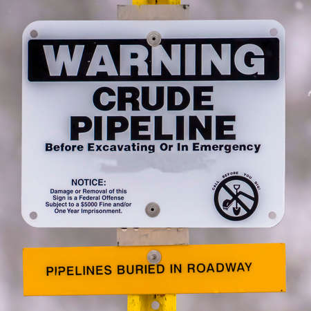 Clear Square Close up of a Warning sign on an area with crude pipeline viewed in winter. The sign warns people about pipelines buried in the roadway. Zdjęcie Seryjne