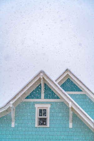 Snow falling on a blue home in Daybreak Utah with cloudy sky in the background. The house has sliding glass window and snow covered roof in winter.