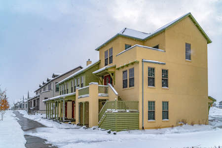 Wet and snowy pathway in front of adorable homes in Daybreak Utah. The snow falling from the cloudy sky creates a blanket of frost on the landscape.