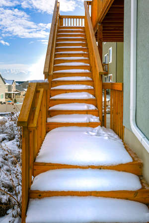 Outdoor wooden staircase of a home covered with snow during winter season. A scenic view of homes, snow capped mountain, and blue sky with puffy clouds can be seen in the background. Stok Fotoğraf