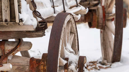Panorama Close up of the rusty wheels of an old wooden wagon viewed in winter. The wagon and the rocky terrain is blanketed with powdery white snow.
