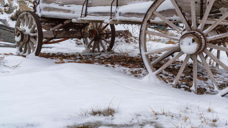 Panorama Wooden cart on a hill with a view of snow capped mountain and cloud filled sky. The weathered cart with rusty wheels is dusted with powdery snow in winter. Фото со стока