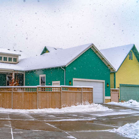 Square Winter view of a colorful home with wooden fence against cloudy sky in Daybreak. A wet and snowy road can be seen in front of the house with frosty roof.