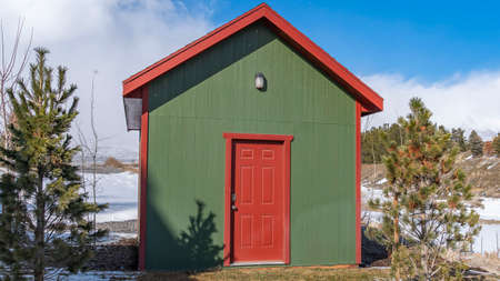 Panorama Small wooden storage shed with a lamp on the green wall above the red door. The terrain surrounding the shed is covered with snow on a sunny winter day. Фото со стока