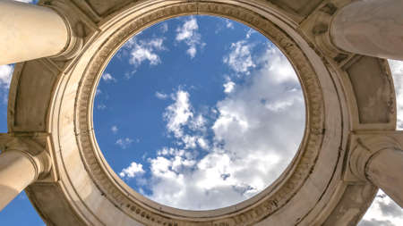 Panorama Circular structure supported by huge columns viewed on a sunny day. A beautiful and vast blue sky with puffy clouds can be seen over the structure.