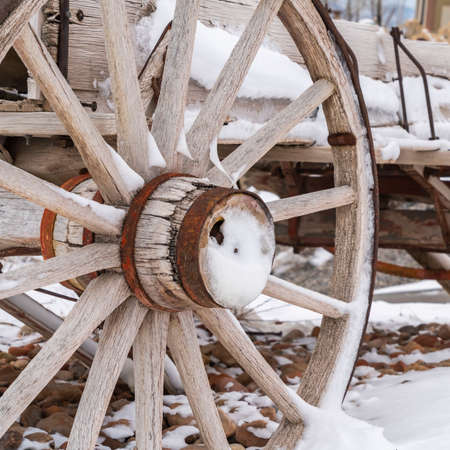 Clear Square Close up of the rusty wheels of a weathered wooden wagon viewed in winter.The wagon and surrounding landscape is covered with fresh powdery snow. 版權商用圖片