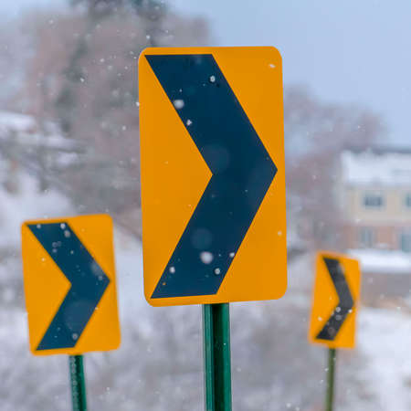 Square Directional road signs against a snowy landscape. Close up of a yellow and black directional road sign in winter. A snow covered landscape with homes and trees can be seen in the hazy background.
