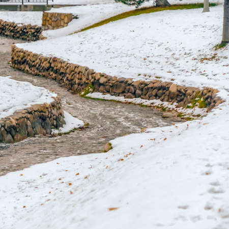 Square Stone lined creek on a park in Salt Lake City viewed on a frosty winter day. The landscape is blanketed with powdery white snow during this cold season. 版權商用圖片