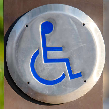 Square Close up of a Disabled Sign engraved on a circular metal viewed on a sunny day. The sign indicates an area that is adapted for wheelchair users.