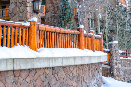 Building in Park City Utah with wooden railings and mosaic stone wall. Powdery white snow can also be seen in the landscape during winter season. 版權商用圖片