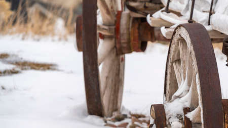 Clear Panorama Close up of the rusty wheels of an old wooden wagon viewed in winter. The wagon and the rocky terrain is blanketed with powdery white snow.