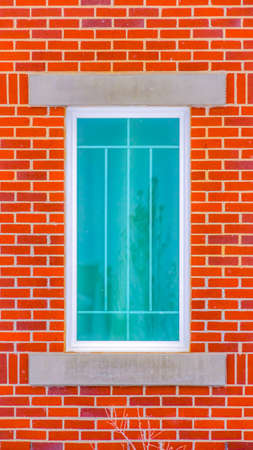Clear Vertical Close up of the rectangular window of a building with red brick wall. Reflection of a building, tree, and sky can be seen on the glass window. Stock Photo - 122766617