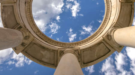 Clear Panorama Circular structure supported by huge columns viewed on a sunny day. A beautiful and vast blue sky with puffy clouds can be seen over the structure.