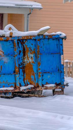 Vertical bin on the snow covered ground against houses in Daybreak Utah.