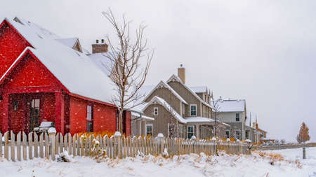 Panorama Footprints on powdery snow along the charming homes at winter time in Utah. The charming homes have snowy roofs and low wooden picket fences. Фото со стока