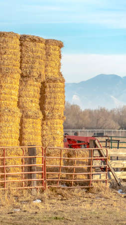 Clear Vertical Blocks of hay piled inside a fenced area on a farm in Eagle Mountain Utah. A scenic background of mountain and sky can be seen on this sunny winter day. Banque d'images - 122766673