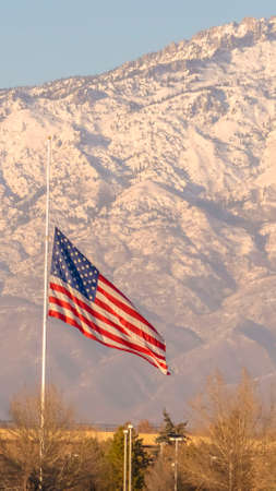 Vertical American flag and building with Mount Timpanogos and sky in the background. The majestic mountain is capped with snow on this sunny winter day in Eagle Mountain, Utah.