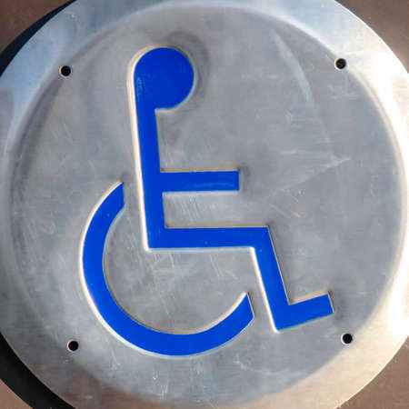 Clear Square Close up of a Disabled Sign engraved on a circular metal viewed on a sunny day. The sign indicates an area that is adapted for wheelchair users. Banco de Imagens
